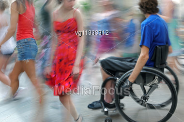 Handicapped Person On A Wheelchair , People Walking By Stock Photo