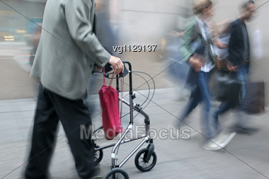 Handicapped Senior Citizen With Walker In Motion Blur, Couple Passing By Stock Photo