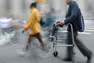 Handicapped Senior Citizen With Walker In Motion Blur, Walking Woman Passing By Stock Photo
