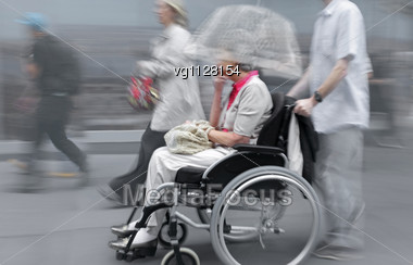 Handicapped Senior Person On A Wheelchair With Assistant Stock Photo