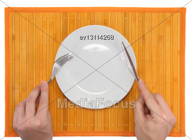 Hands Hold Fork And Knife Above Plate On Bamboo Mat. All Around Isolated Stock Photo