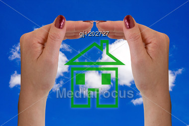 Hands And Icon House Over A Sky Background Stock Photo