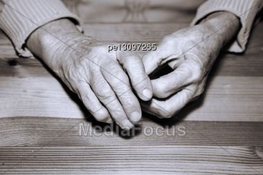 Hands Of The Old Person On A Table Stock Photo