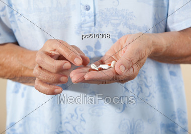 Hands Of A Senior Citizen With Pills Stock Photo