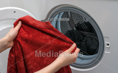 Hands Placing The Clothes In The Drum Of Washing Machine Stock Photo