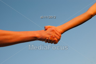 Hands Shaking Each Other Against Blue Sky Stock Photo