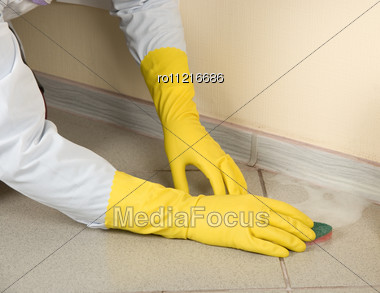 Hands In Yellow Gloves With Sponge, Washing Floor And Plinth Stock Photo