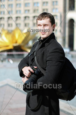 Handsome Man Wearing Black Clothes And Posing With Camera Outdoors Stock Photo