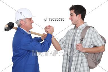 Handyman Handshaking His Trainee. Stock Photo