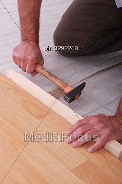 Handyman Laying Floorboards Stock Photo