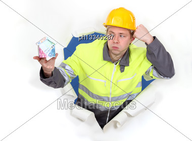 Handyman Presenting A Miniature House Made Of Euro Bills Stock Photo