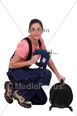 Handywoman Holding A Jigsaw And An Extension Cord Stock Photo