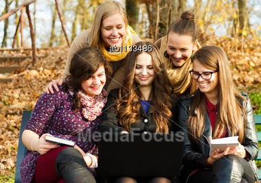 Happy Beautiful Students Using A Laptop Stock Photo
