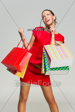 Happy Beautiful Young Woman Wearing Red Dress And Sunglasses Standing With Lots Of Shopping Bags Stock Photo