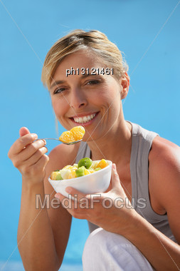 Happy Blond Woman Eating Fruit Salad Stock Photo