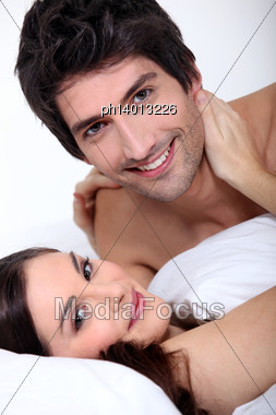 Happy Couple Kissing In Bed Stock Photo