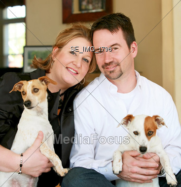 Happy Couple with Their Dogs Stock Photo