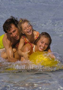 Happy family embracing in the waves at the beach Stock Photo