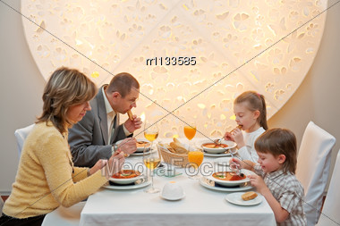 Happy Family Enjoying Meal Sitting At Restaurant Table Stock Photo