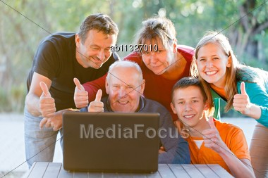 Happy Family Showing Thumbs Up For Technology Stock Photo