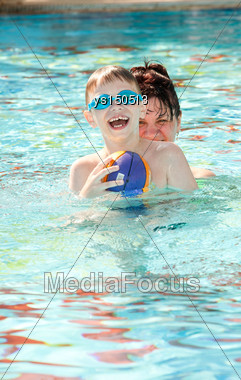 Happy Mother And Son Playing In The Pool Stock Photo