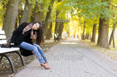 Happy Pretty Young Brunette Sitting On A Bench In Autumn Park Stock Photo