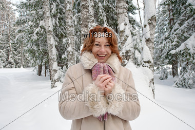 Happy Red-haired Woman Having Fun On Winters Day In Forest. Stock Photo