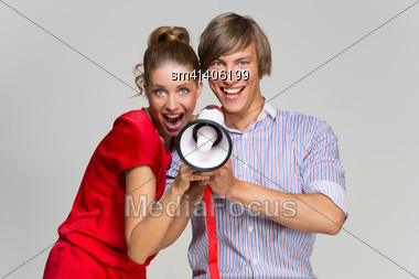 Happy Young Beautiful Couple Screaming At Mehaphone Over Grey Background Stock Photo