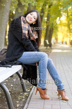 Happy Young Brunette Sitting On A Bench In Autumn Park Stock Photo