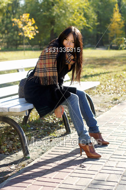Happy Young Woman Sitting On A Bench In Autumn Park Stock Photo