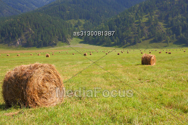 Hay Rolls In The Background Of Mountains Stock Photo