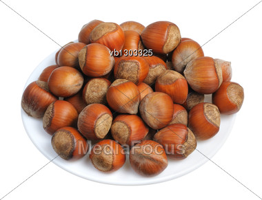 Hazelnuts On A White Plate On A White Background, Isolated Stock Photo