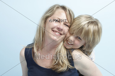 Head And Shoulders Image Of A Blond Woman With Her Blond Son Nestling His Chin On Her Shoulder Stock Photo