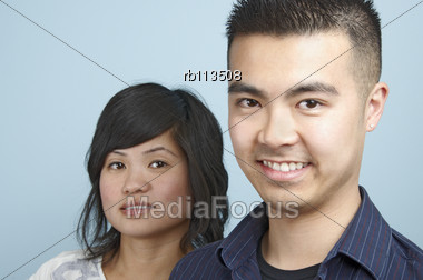 Headshot Of A Young Asian Female With A Young Asian Male Head In The Foreground Stock Photo