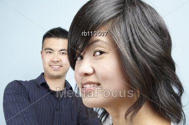 Headshot Of A Young Asian Male With A Young Asian Female Head In The Foreground Stock Photo