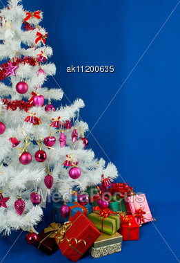 Heap Of The Christmas Presents Under Decorated White Evergreen Tree Stock Photo