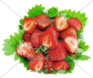 Heap Of Fresh Strawberries In Glass Bowl On Green Foliage . Isolated Stock Photo