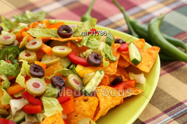 Heap Of Nachos With Vegetables On Green Plate Stock Photo