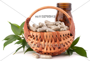 Herbal Drug Capsules In Wicker Basket Isolated On White Background Cutout. Alternative Medicine Concept Stock Photo
