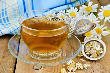 Herbal Tea In A Glass Cup, A Metal Strainer With Dried Chamomile Flowers, Fresh Flowers Daisies, Napkin Against A Wooden Board Stock Photo