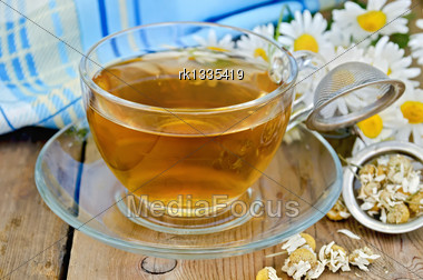 Herbal Tea In A Glass Cup, A Metal Strainer With Dried Chamomile Flowers, A Bouquet Of Fresh Chamomile Flowers, Napkin Against A Wooden Board Stock Photo