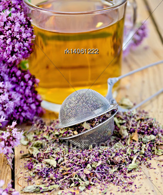 Herbal Tea In Glass Mug, Metal Sieve With Dry Flowers Marjoram, Fresh Flowers Of Oregano On The Background Of Wooden Boards Stock Photo