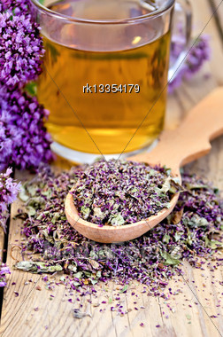 Herbal Tea Of Oregano In A Glass Mug, A Spoon With Dried Flowers Of Oregano, Marjoram Bouquet Of Flowers On A Background Of Wooden Boards Stock Photo