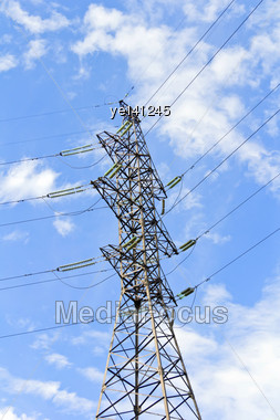 High Voltage Power Lines And Large Pylon Above Blue Sky Stock Photo