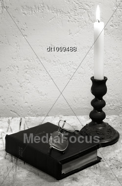 Holy Bible On The Desk With Burning Candle Stock Photo