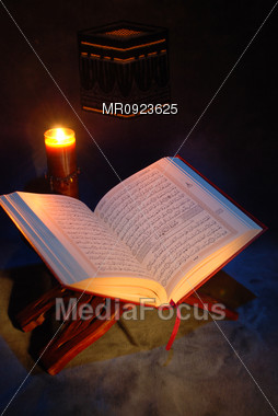 The Holy Quran and lighting Candle Stock Photo