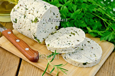 Homemade Cheese With Herbs And Spices Cut Into Slices, Knife, Parsley, Rosemary, Vegetable Oil In A Bottle On A Wooden Board Stock Photo