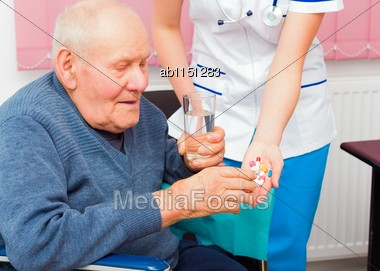 Hospital Services For Elderly In Wheelchair, Young Nurse Helping Senior Patient Stock Photo