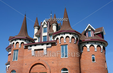 House With A Beautiful Roof With Windows And Carved Domes From A Red Brick. Stock Photo