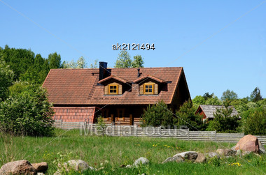 House With A Tile On A Background Of Plants Stock Photo